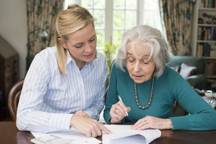 Younger woman and older woman reviewing a legal document, such as Power of Attorney