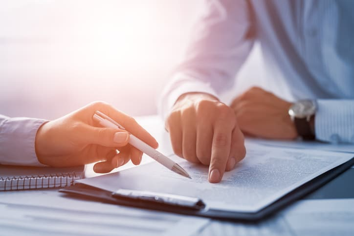 Hands working with documents at desk and signing a document, possibly a Trust.