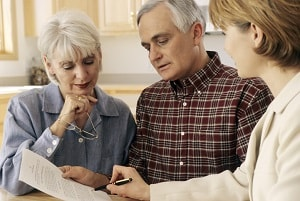 Mature couple talking to estate planning lawyer at home