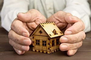 Old man protecting house model with hands, Asset Protection