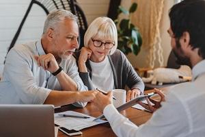 Estate planning lawyer explaining Trust paperwork to senior couple